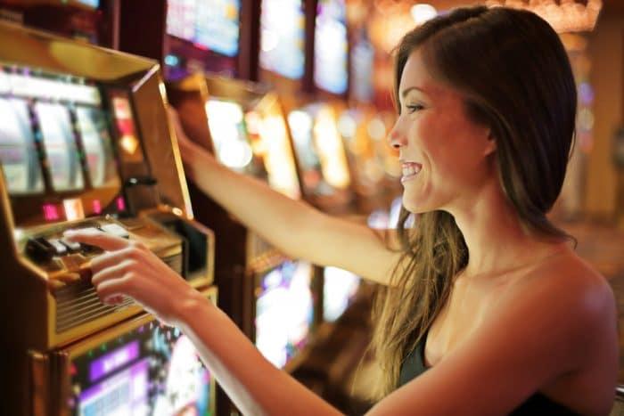 Woman playing slot machine at Casino